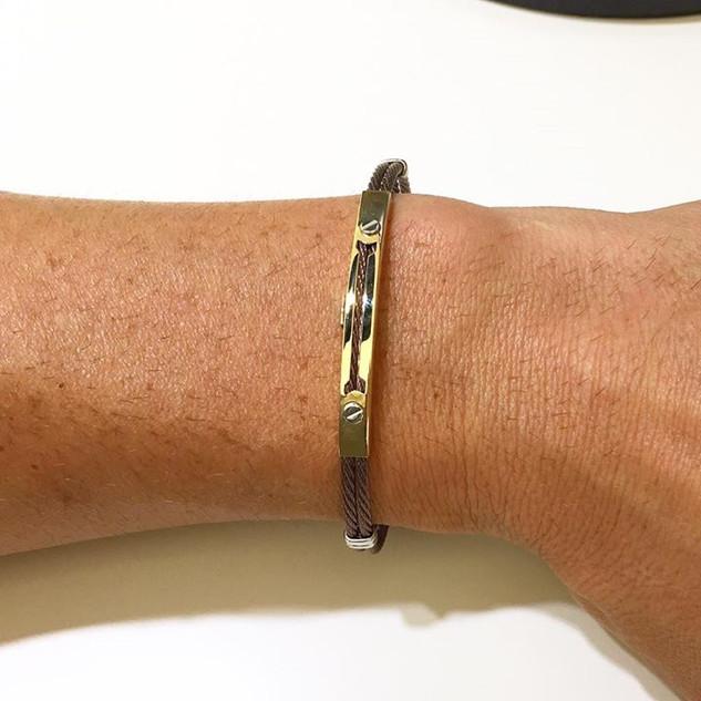 Bracciale fashion con cordone flessibile in acciaio color ramato e piastrina in oro giallo 18 kt . Price € 225,00