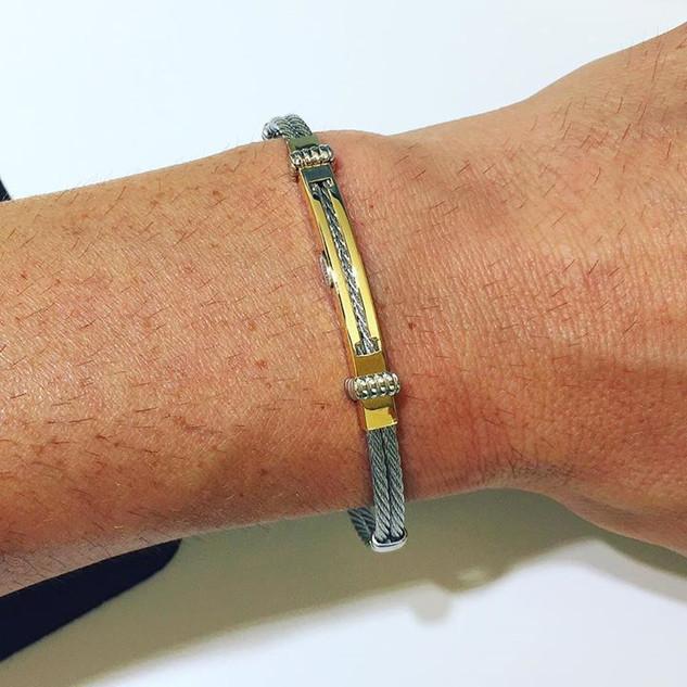 Bracciale fashion con cordone flessibile in acciaio colore grigio e piastrina in oro giallo 18 kt . Price € 245,00