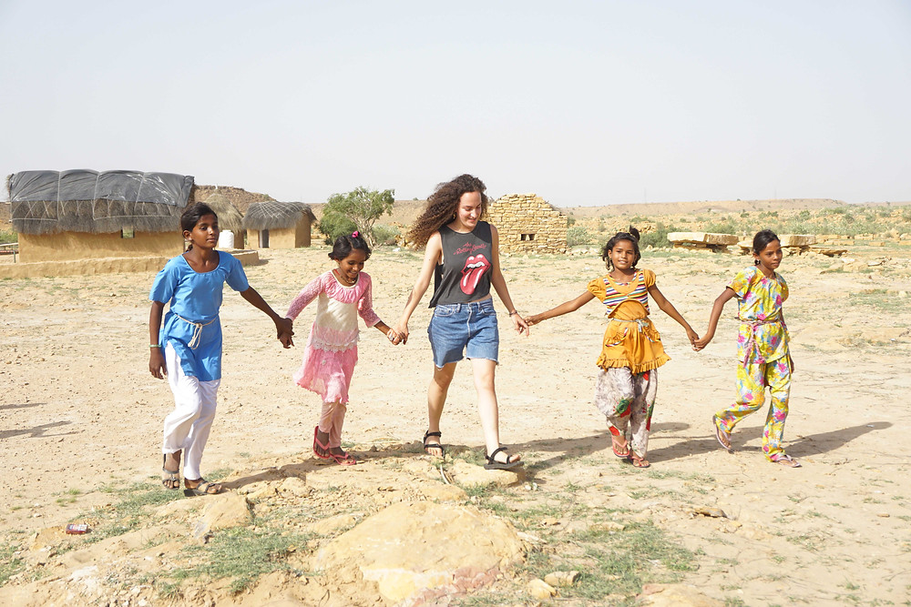 Maya from Israel receives a tour of Mala Ki Dhani from local girls.