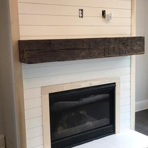Reclaimed hand hewn oak timber mantel with custom finish on shiplap