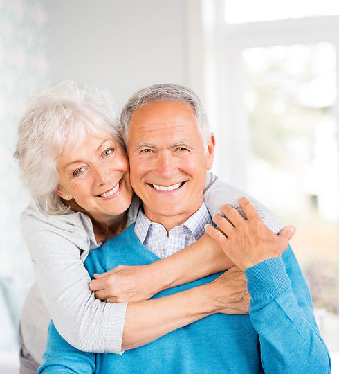 cheerful senior couple embracing at home