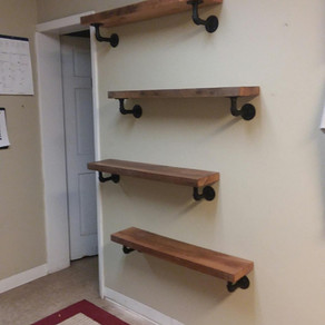 Installing reclaimed oak shelves with plumbing pipe in our office managers space