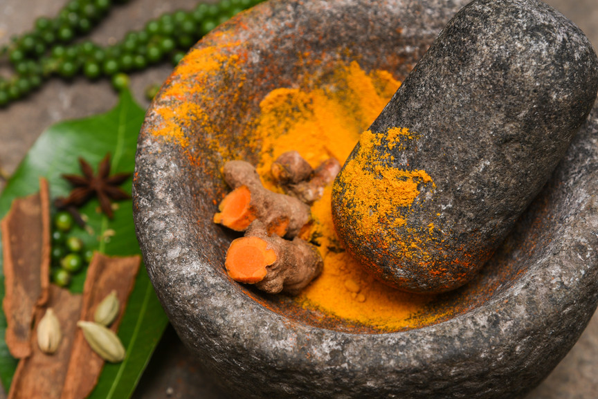turmeric roots and powder in a mortar Ke
