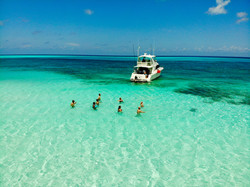 Custom Mexico Vacation | GeoLuxe Travel LLC | people standing in the ocean near a boat