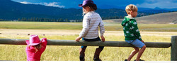 Custom Alaska and US Vacation   GeoLuxe Travel   children sitting on a fence