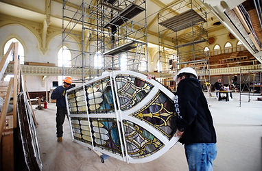 Crews install restored stained glass win