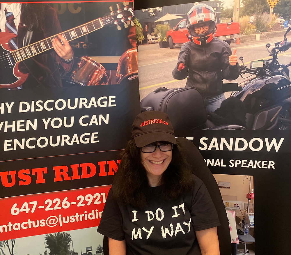 Angie sitting infront of her JUSTRIDIN banners as she presents her story about how breast cancer motivated her to ride with one hand at the Online Women's Motorcycle Conference