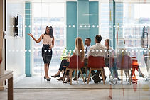 Workshop of 4 to 6 people sitting at a table listening to a woman speaker