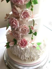 4-Tier white fondant wedding cake with a ruffle bottom tier and rose & bud leaf cascade