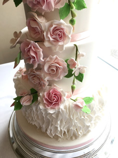 4-Tier white fondant wedding cake with a ruffle bottom tier and rose & bud leaf cascade