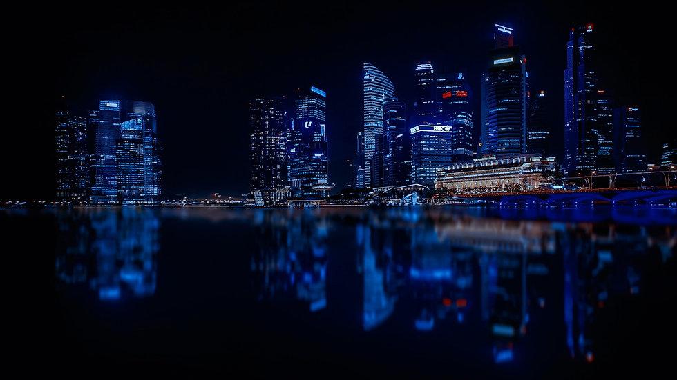 illuminated-cityscape-against-blue-sky-a