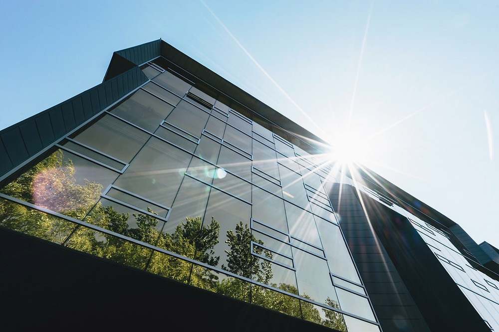 Photo of a modern building with staggered glass window panels, shot upward with a sun burst off center to the right behind the building