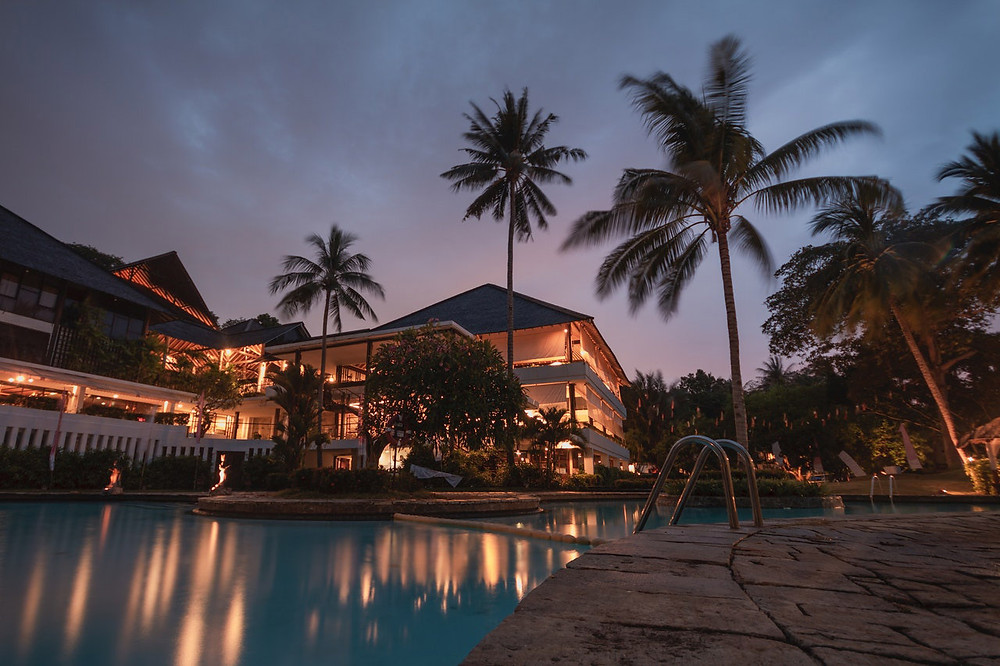 Photo at dusk of a well-lit luxury multi-tenant property with palm trees