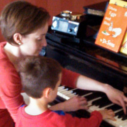 cousins at piano lesson on a sunday get together...one teaching, one learning..