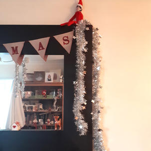 Elf on the Shelf helps to hang the tinsel
