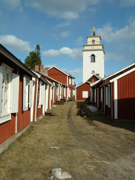 Gammelstads kyrkstads kyrka i bakgrunden och röda stugor i förgrunden