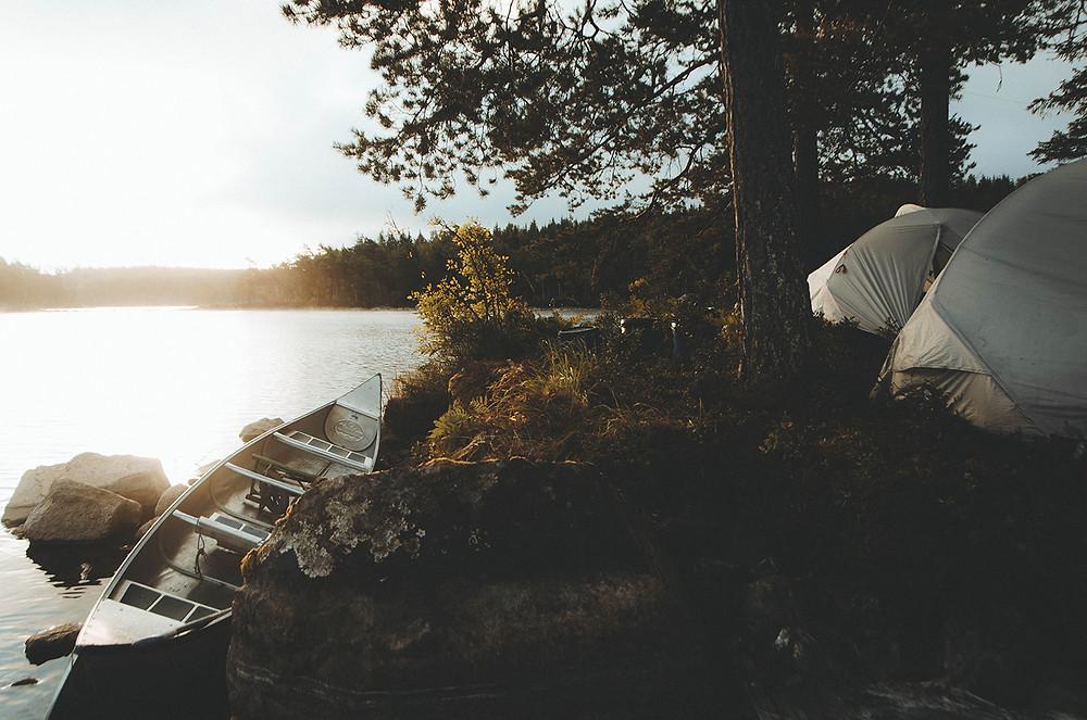 Kanoter och tält vid en sjö i Sverige.
