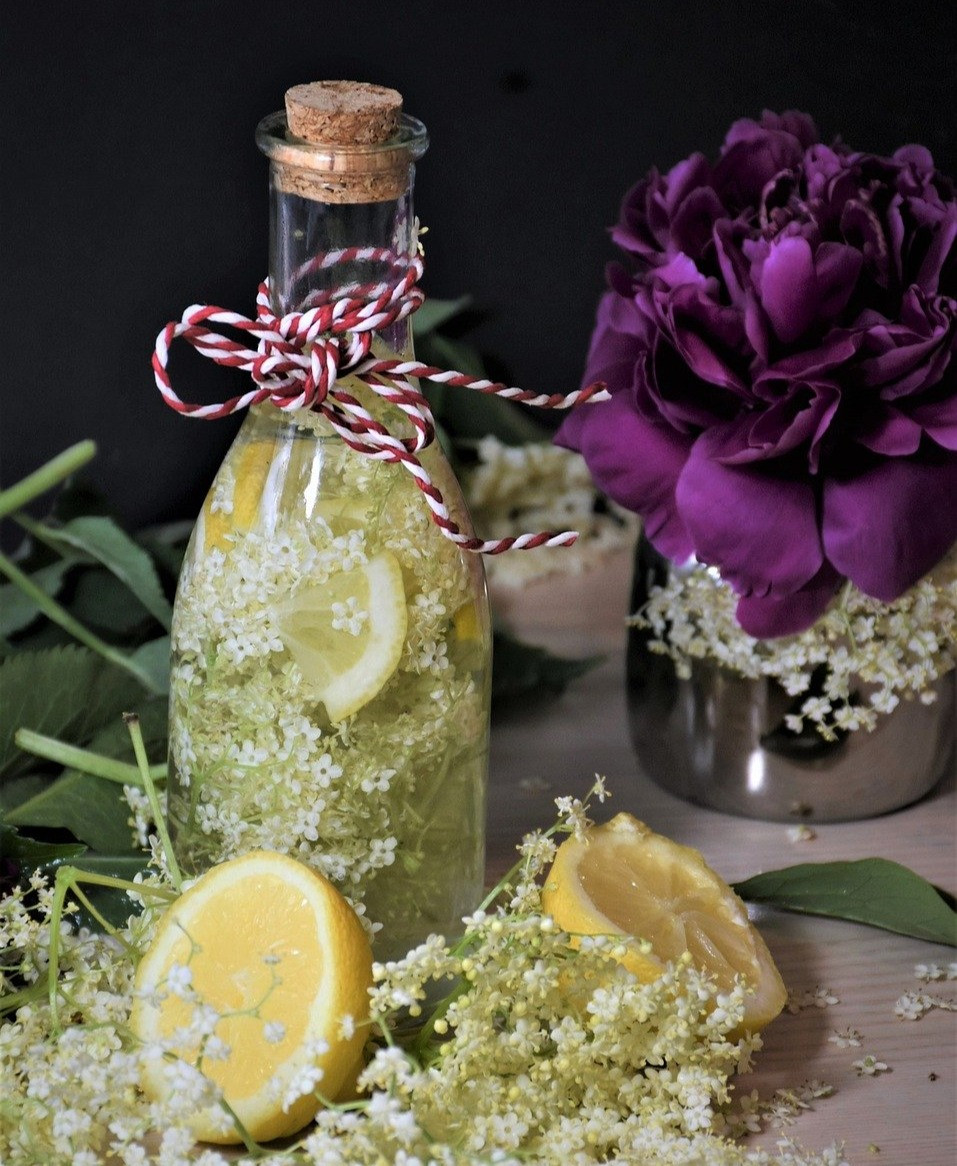 Flädersaft i flaska med fläder och citron intill