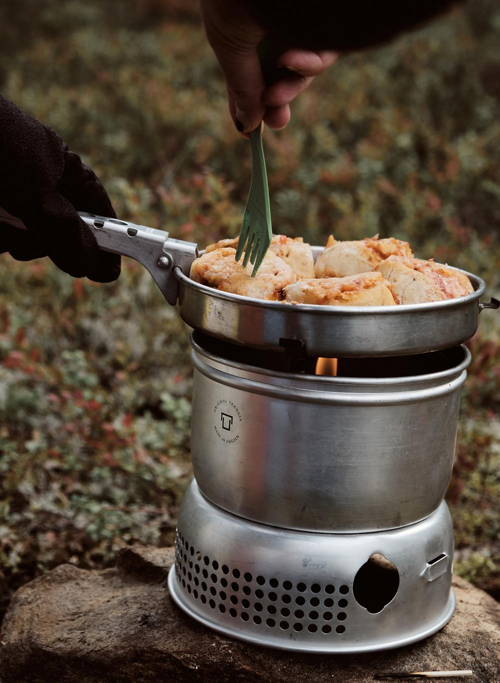 Matlagning på trangiakök på campingen