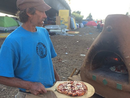 An Oven in The Village Homeless Encampment Provides Warmth and Wood-Fired Pizza    by Momo Chang