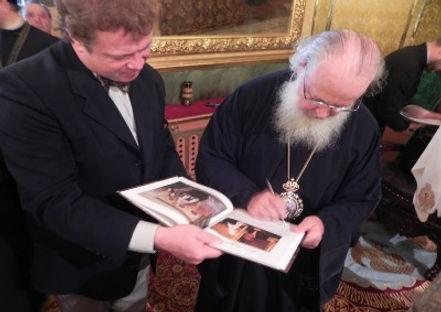 Патриарх расписывается в книге Игоря Баб