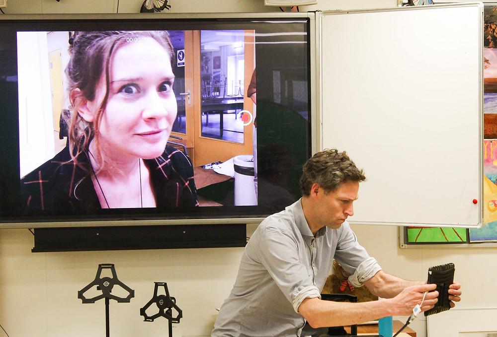 Een foto van een vakdocent die aan het filmen is met een tablet. Achter hem op het grote scherm is te zien wat hij aan het filmen is. Op dit scherm zie je het gezicht van een vrouw.