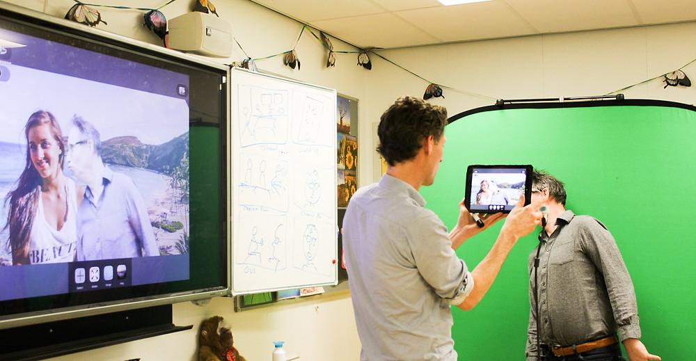 Een foto van een vakdocent die laat zien hoe een green screen werkt. Hij filmt een cursist met een tablet voor het green screen. Op het scherm links is te zien dat er een achtergrond bij het videobeeld is toegevoegd. Het geeft de illusie dat de cursist een kus geeft aan een vrouw.
