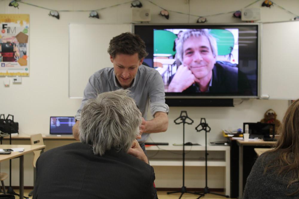 Een foto van een klaslokaal met een groot scherm. In het lokaal is een vakdocent een film aan het maken van het gezicht van een cursist. Deze filmshot is te zien op het grote scherm achter de mannen.