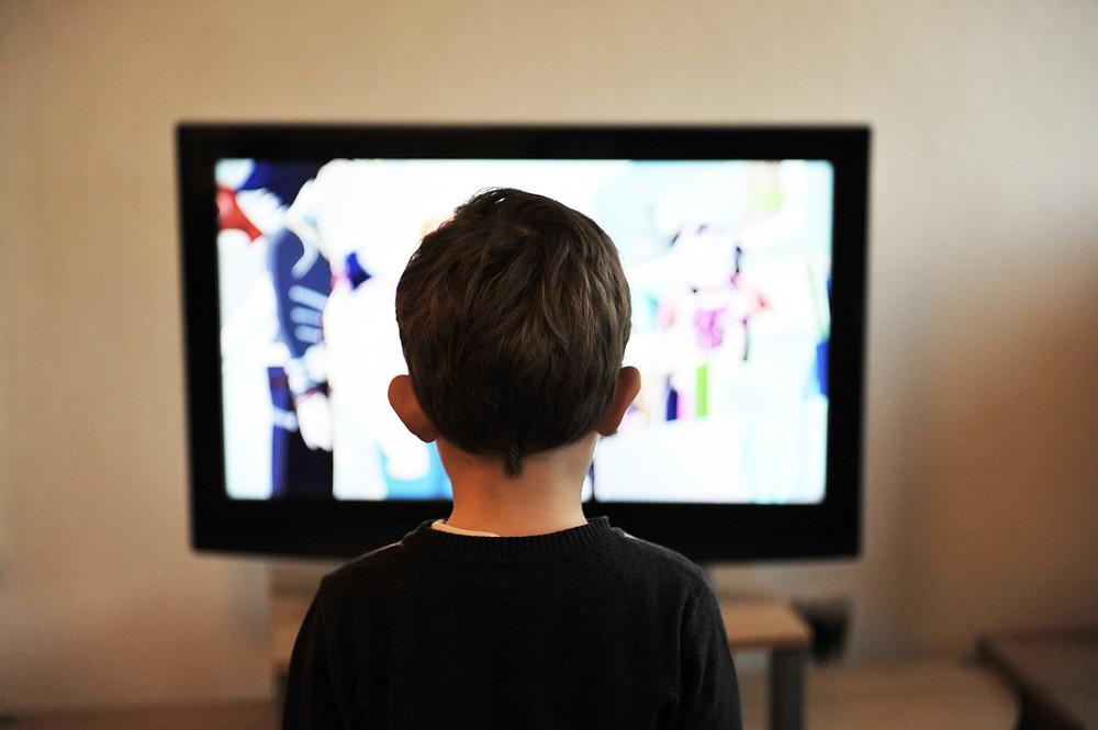 Een foto van een jong kind dat voor een televisie scherm zit. Dit jongetje zie je van de achterkant, zijn rug. Hij kijkt naar dit scherm waar bewegend beeld in kleur op te zien is.