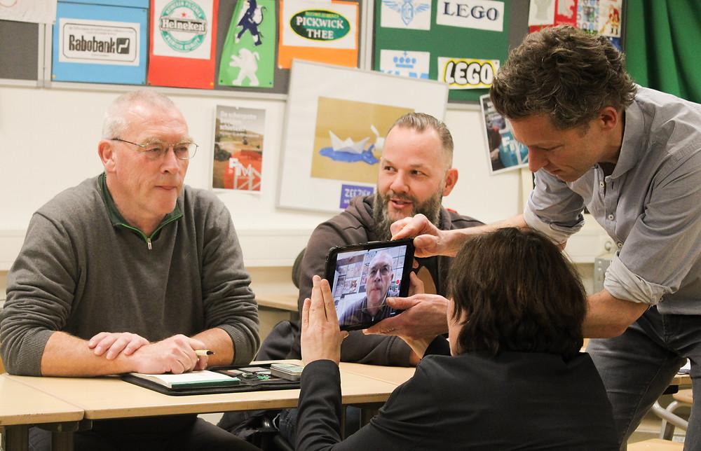 Een foto van een vakdocent die aan drie cursisten aan het uitleggen is hoe je met een tablet kan filmen. Een van de cursisten filmt met de tablet een andere cursist.