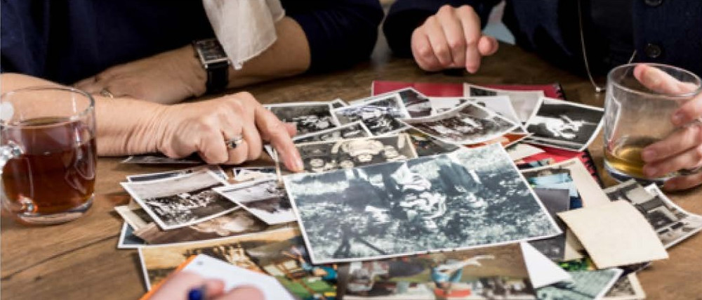 Een foto van een tafel met daarop een stapel oude zwart wit en gekleurde analoge foto's. Aan deze tafel zitten twee personen die tot schouderhoogte te zien zijn. Ze wijzen beide naar een foto. Op de tafel staan ook twee kopjes thee.