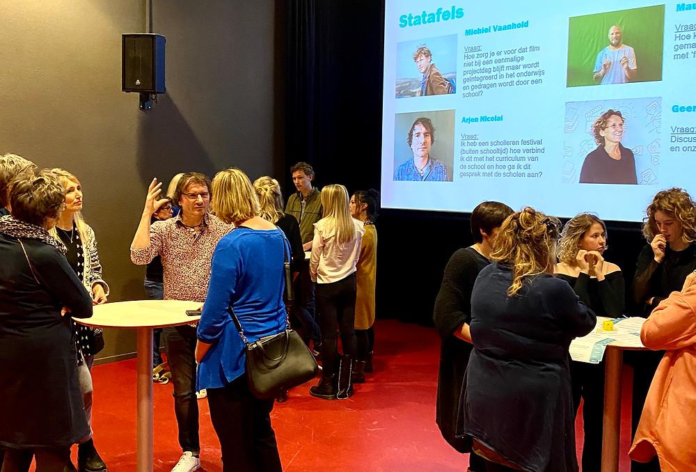 Een foto van een podium in een theaterzaal met een groot projectiescherm. Op dit scherm staan foto's van vier verschillende mensen met een beschrijving. Op het podium staan drie stamtafels waar mensen met elkaar in gesprek zijn.