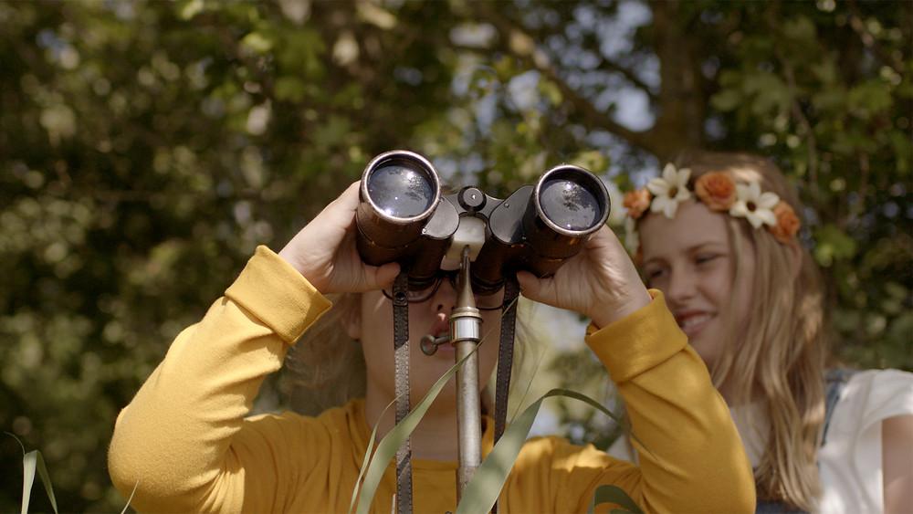 Een foto van een kind dat buiten in de natuur door een verrekijker kijkt. Achter haar staan een meisje met een bloemenkrans in haar haren.