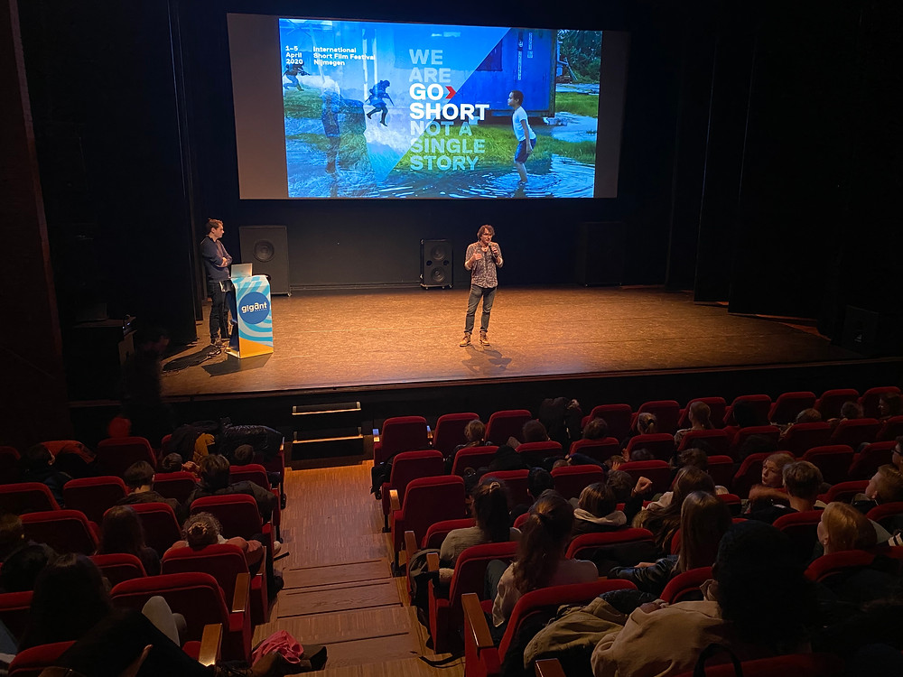 Presentatie van een man op een podium voor een diascherm. Op het diascherm zie je een afbeelding van Go Short. Daarop staat de titel 'we are go short not a single story' en zie je kinderen spelen in waterplassen.