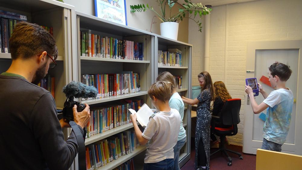 Een foto van een groep van vijf kinderen staat voor een kast vol boeken. De kinderen kijken in de boeken. Een jongen zit de kinderen te filmen met een tablet. Een man staat links de totale groep te filmen met een camera.