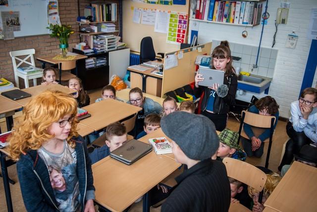 Een foto van een klas op een basisschool. Twee kinderen zijn verkleed en spelen een scène voor een film. Een ander kind film met een tablet. De rest van de klas zit gehurkt tussen de tafeltjes te kijken naar de filmscène.