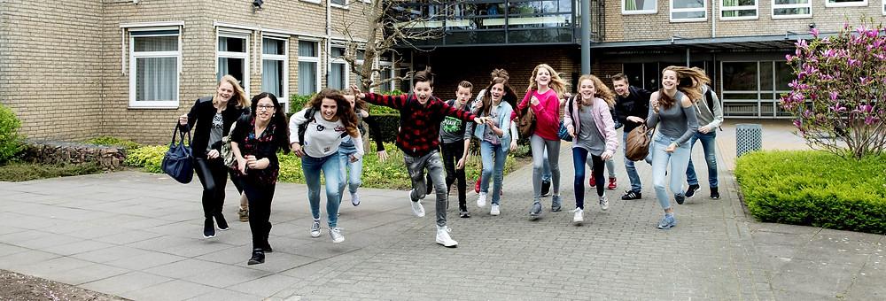 Een foto van een groep leerlingen die uit een school aan het rennen zijn. De leerlingen kijken vrolijk.