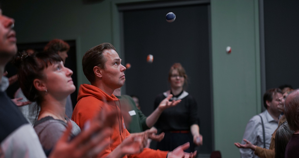 Een foto van een groep met volwassen mensen die met balletjes aan het jongleren zijn. De focus in de foto ligt op een man met een oranje trui aan.