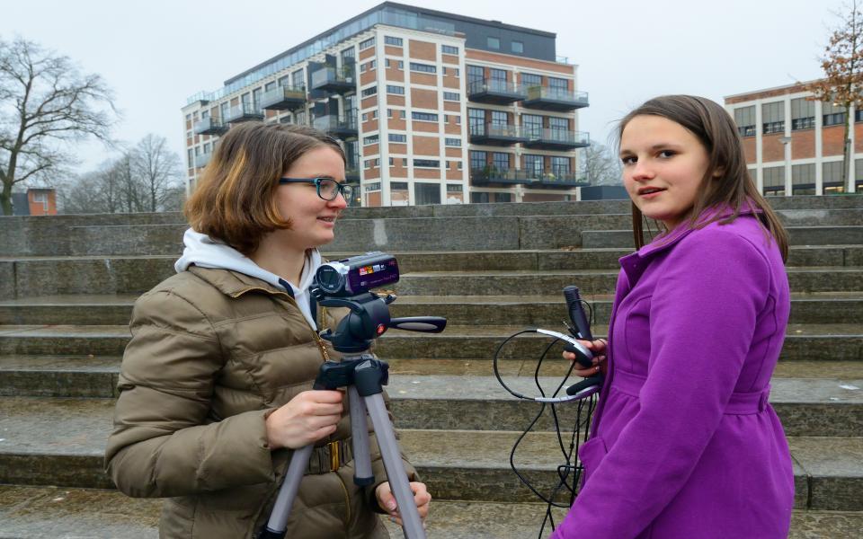 Een foto van twee meisjes die buiten aan het filmen zijn bij een stenen trap. Het meisje links houd een camera vast op een statief, het meisje rechts heeft een microfoon en koptelefoon in haar hand.