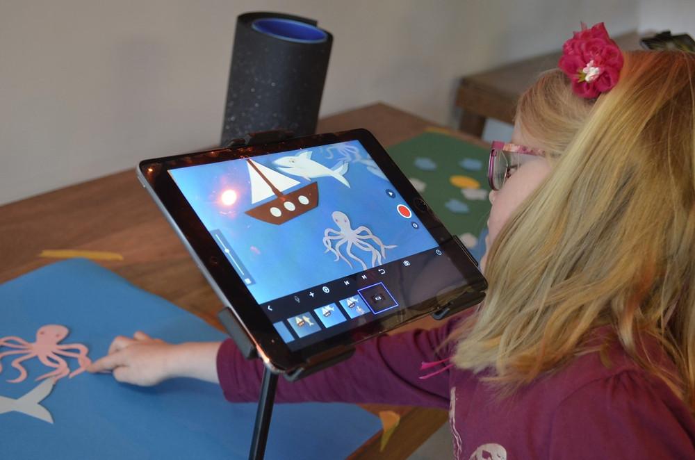 Een foto van een meisje met een bloem in haar haren dat aan tafel zit. Het meisje is bezig om een stop-motion film te maken met een tablet. Ze maakt foto's van een blauw vel papier met daarop uitgeknipte figuren uit de zee, zoals een boot, haai en octopus. Deze verschuift ze met haar handen.