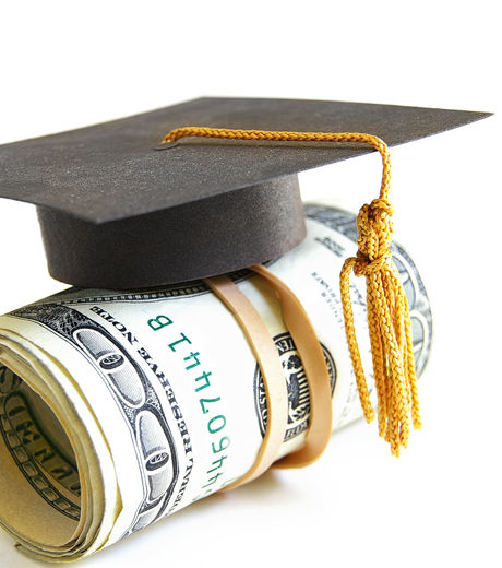 mini graduation cap on a roll of money.j