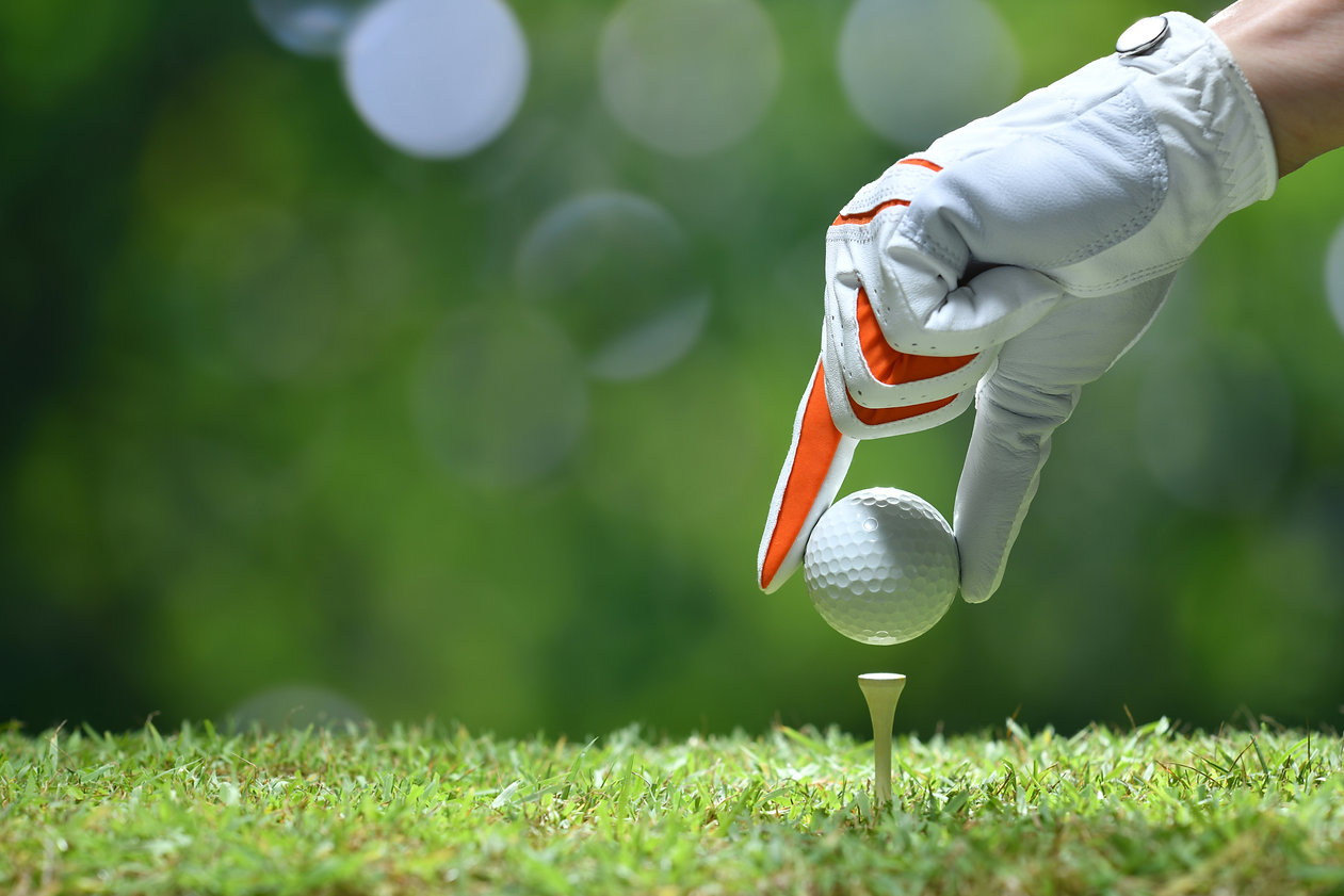 Hand hold golf ball with tee on golf cou