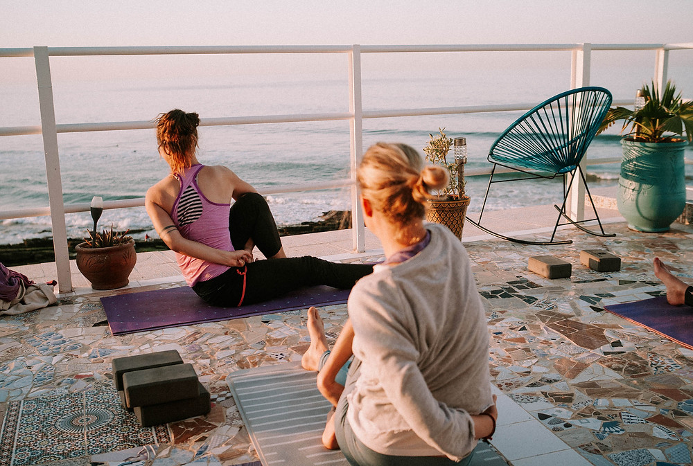 Two women practicing yoga face the calm sea on a sunny terrace