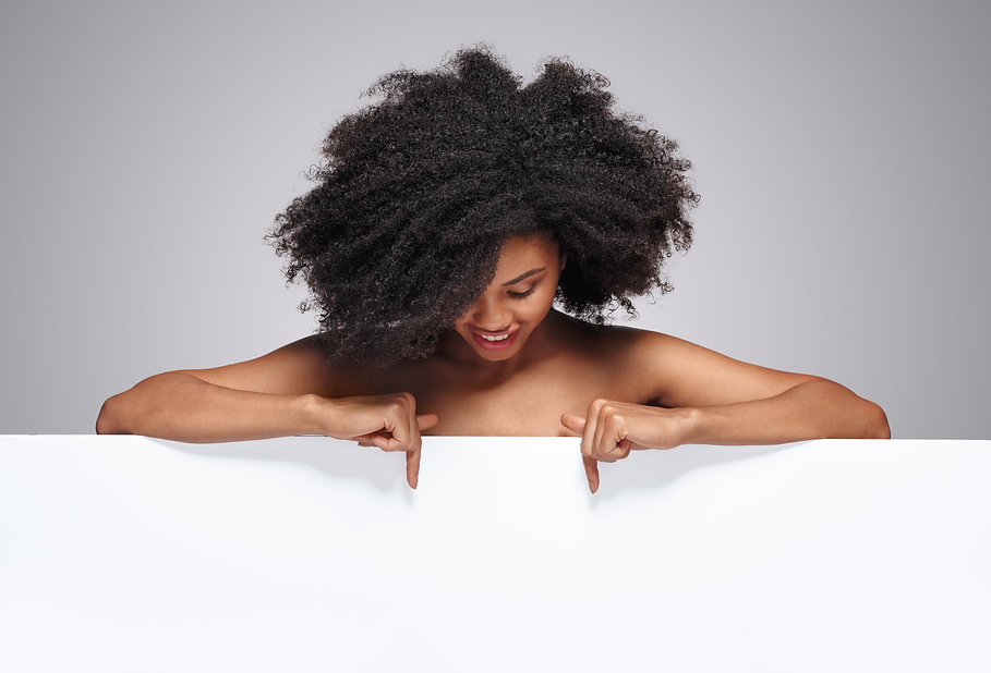 Happy black female with curly hair looki