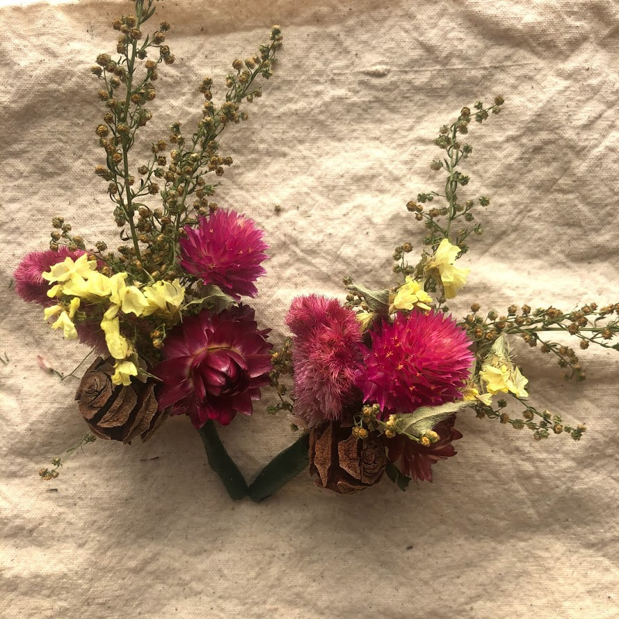 A set of everlasting boutonnieres with pink and yellow dried flowers.