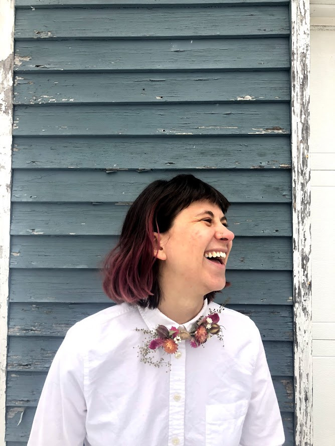 Meg, laughing, wearing a white button up and a peachy everlasting bowtie, made with dried flowers.