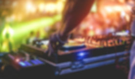 Dj mixing outdoor at beach party festival with crowd of people in background - Summer nightlife view