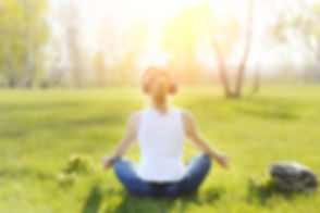 Young woman sitting on grass in Park and meditating and listening to music on headphones