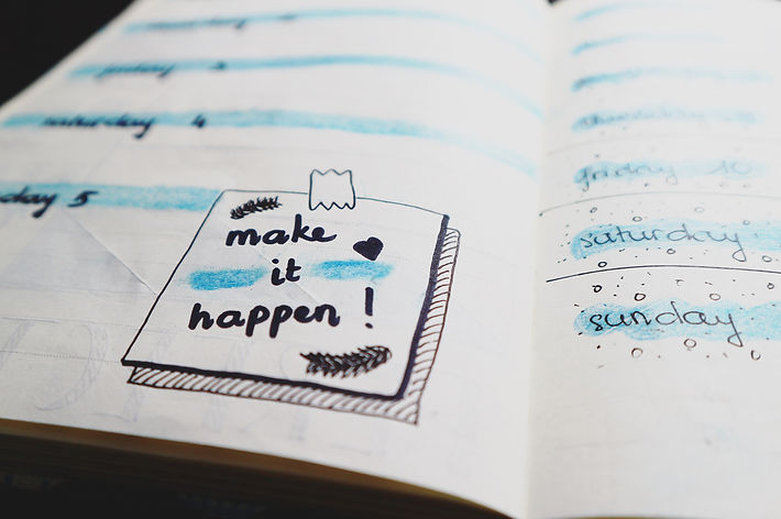 Note book open with a doodle that says 'Make it happen!'
