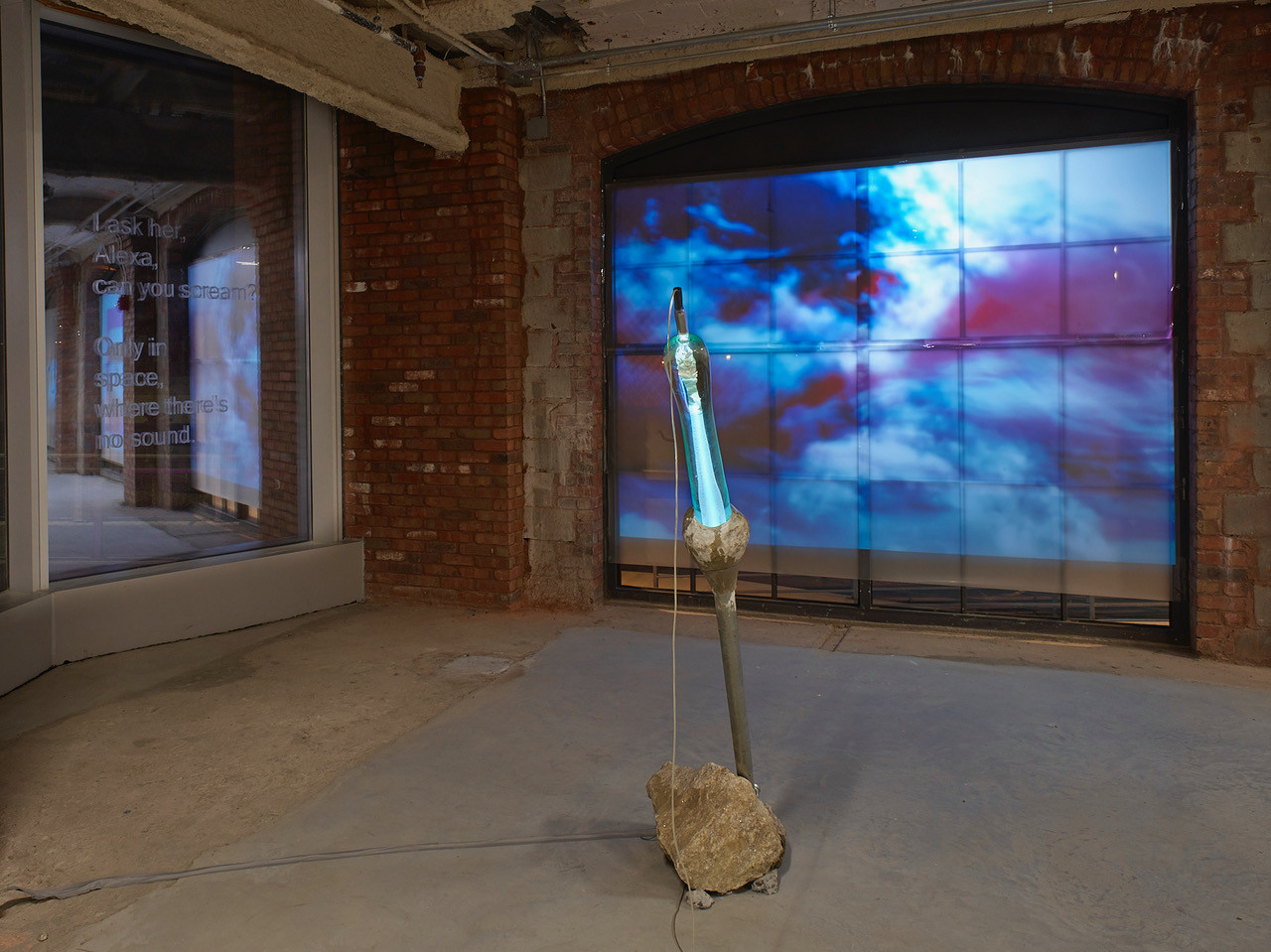 """left to right  Amanda Turner Pohan  """"Alexa, can you scream? Only in space, where there is no sound.""""  Excerpt from a conversation with the artist and Amazon's Alexa written in Artificial Cerumen (earwax) on glass window panel  48"""" x 40"""" 2020  Lara Saget and Joshua Raiffe """"Apex""""  Historic sourced Tuckahoe Marble, Historic sourced Tuckahoe Mico, Glass 12 x 12 x 8 inches 2019"""